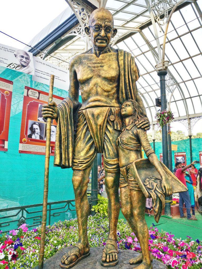 A huge statue of Mahatma Gandhi holding a child